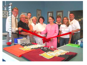 Village Cleaners family and staff cutting the ceremonial opening ribbon.
